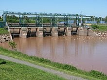 A concrete and steel structure crosses the river. The water is brown on the near side of the structure, and blue on the far side