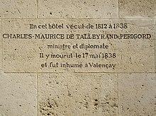 Photo d'un mur de grandes pierres blanches finement jointes, dont une au centre est gravée par les lignes suivantes : « En cet hôtel vécut de 1812 à 1838 / CHARLES-MAURICE DE TALLEYRAND-PERIGORD / ministre et diplomate / Il y mourut le 17 mai 1838 / et fut inhumé à Valençay ».