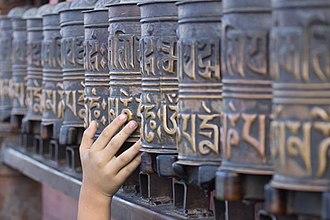Prayer wheel - A little boy rolling the prayer wheels at Swayambhunath, Nepal.