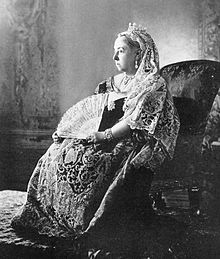 Photograph of a seated woman in embroidered and lace dress staring into the distance, looking sad