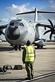 RAF Ground crew member waits to fit chocks to taxing A400M (ATLAS). MOD 45158531.jpg