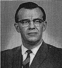 Black-and-white photograph of dark-haired man in suit and wearing glasses