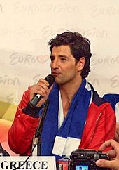 Colorfully-dressed young man speaking into a hand-held microphone
