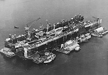 A floating drydock containing ships. It is surrounded by floating barges with workshops and a tugboat.