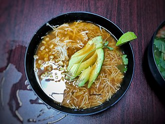 Sopa de fideo - Sopa de fideo with corn and chicken, garnished with avocado and a lime wedge