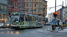 A tram with advertisements at a busy intersection