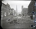 Street workers beside a pile of rubble on a cobblestone street.jpg