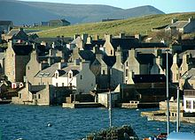 Stone houses crowd around a shore, the gable ends facing the water, with green hills beyond.