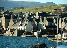 Les maisons en pierre se pressent autour d'un rivage, le pignon face à l'eau, avec des collines verdoyantes au-delà.