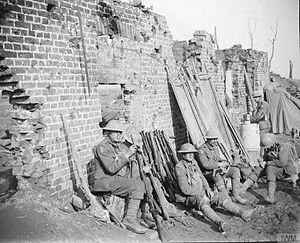Dorset Regiment - Troops of the Dorsetshire Regiment resting and cleaning rifles in the ruins of a farm near Langemarcke, 17 October 1917.