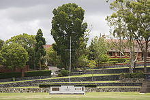 A grassy playing field with a war memorial at the end. Above the memorial are terraced steps leading up to trees and a chapel.