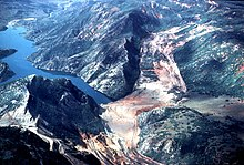 An aerial picture of a de-stabilized mountain sliding and creating a dam and lake. Various construction activity is present to the left of the slide area.