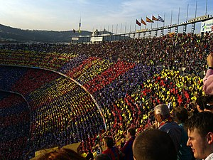 A crowd of spectators in an open-air stadium, a mosiac in red, blue and gold is visible