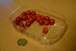 Tomberries next to a British pound coin