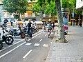 Two-way bikeway turns the corner between motorcycle parking and curb (18605406700).jpg
