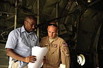 U.S. Air Force Tech. Sgt. Owen Duke Jr., right, a C-130H Hercules aircraft loadmaster assigned to the 746th Expeditionary Airlift Squadron, goes over paperwork with a U.S. Embassy representative before unloading 100822-F-KV470-053.jpg