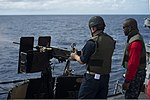 U.S. Navy Chief Gunner's Mate Timothy Russell, right, supervises Midshipman Jeremy Brazel as he shoots a .50-caliber machine gun on the bow of the guided missile destroyer USS Preble (DDG 88) in the Solomon 130807-N-TX154-158.jpg