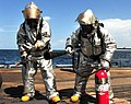 U.S. Navy Damage Controlman 2nd Class Nicholas Brown, left, and Counselor 1st Class Robert Ehrhart extinguish a simulated fire on the flight deck of the guided missile frigate USS Underwood (FFG 36) as part of 120905-N-ZE938-059.jpg