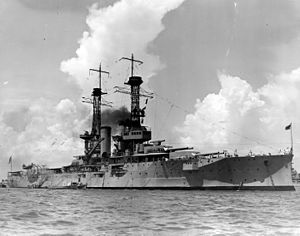 A large light gray battleship sits in harbor, dark black smoke billows lazily from the central smoke stacks