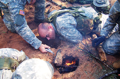 US Army aviation SERE students create a Dakota hole to conceal a fire in order to better protect their position from enemy observation. US Army SERE Training Photo.png