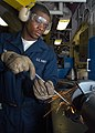 US Navy 030515-N-1512S-028 Fireman Apprentice Aaron Graham grinds down a rod in the ship's Electrical Motor Rewind Shop.jpg