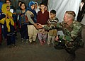 US Navy 051108-N-1261P-065 A U.S. Navy Seabee, assigned to Naval Mobile Construction Battalion Seven Four (NMCB-74), shakes the hands of young Pakistani children.jpg
