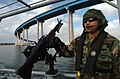 US Navy 061211-N-8252J-134 Operation Specialist 1st Class Jaysen Mendoza, assigned to Inshore Boat Unit Five One (IBU-51), mans a M60 machine gun while conducting boat maneuvers.jpg