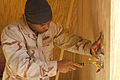 US Navy 061220-N-0193M-036 Construction Electrician 2nd Class Nathaniel Steward inserts a plastic casing around wires that will eventually become a light switch.jpg
