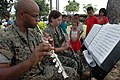 US Navy 070630-N-9421C-099 Local children watch as Cpl. David Street and Lance Cpl. Victoria Holman, both attached to the U.S Marine Forces Pacific Band, perform for patients waiting to be seen by the Pacific Partnership 2007 m.jpg