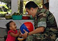 US Navy 070823-N-1467K-050 Lt. j.g. Orlando Rivera, embarked aboard amphibious assault ship USS Peleliu (LHA 5), plays with a Micronesian girl during a medical civic action program at the Malem city government building in suppo.jpg