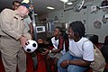 US Navy 070929-N-8704K-025 Capt. Bob Kapcio, mission commander for Military Sealift Command hospital ship USNS Comfort (T-AH 20), gives a soccer ball to a young boy as his mother looks.jpg