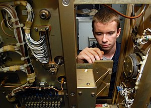 Electronics - Electronics Technician performing a voltage check on a power circuit card in the air navigation equipment room aboard the aircraft carrier USS ''Abraham Lincoln'' (CVN 72).