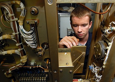 Electronics Technician performing a voltage check on a power circuit card in the air navigation equipment room aboard the aircraft carrier USS Abraham Lincoln (CVN 72). US Navy 080820-N-9079D-007 Electronics Technician 3rd Class Michael J. Isenmann, from St. Louis, Mo., performs a voltage check on a power circuit card in Air Navigation Equipment room aboard the aircraft carrier USS Abraham Lin.jpg