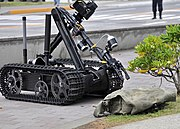 US Navy 090512-N-2013O-013 A Mark II Talon robot from Explosive Ordnance Disposal Mobile Unit 5, Det. Japan, is used to inspect a suspicious package during a force protection-anti-terrorism training exercise