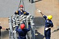 US Navy 090520-N-7478G-328 Fire Controlman 2nd Class Jason Schannot holds the wire steady as Gunner's Mate James Wanless acts as crane rigger and directs the offload of ammunition.jpg