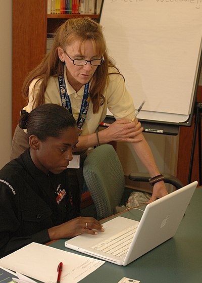 US Navy 091104-N-7434C-080 Kirsten Trussler, a relief services assistant for the Navy and Marine Corp Relief Society, shows information Systems Technician Kimberly Parker how to use budgeting software.jpg