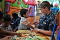 US Navy 111025-N-WW409-113 Ensign Margaret Morton, assigned to the guided-missile destroyer USS Mustin (DDG 89), plays with children at the Pattaya.jpg