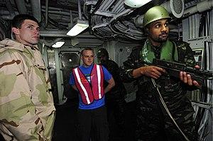 US Navy 120202-N-IZ292-052 Royal Moroccan Navy sailors direct Damage Controlman 3rd Class Brandon Watkins, simulating a captive, past the quarterde.jpg