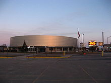A brightly lit hockey arena, clad in metal panels.