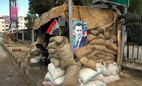 A poster of Bashar al-Assad at a checkpoint on the outskirts of Damascus VOA Arrott - A View of Syria, Under Government Crackdown 05.jpg