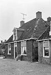 foto van Pand met ingang in het midden onder schilddak met hoekschoorstenen en dakkapel