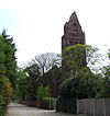 A tall narrow tower with a small pointed spire surrounded by trees in leaf almost hiding the body of the church; to the left is a footpath with railings and a wall