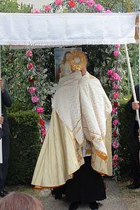 Úrfelmutatás a virágsátorral díszített oltárnál