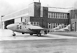 Side view of single-engined, twin-boomed military jet parked in front of a building