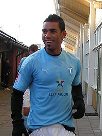 A man wearing a light blue football shirt, white shorts and long black gloves on both hands is seen standing outside a changing room of a football stadium, the man is smiling and looking at something outside the view of the photograph.