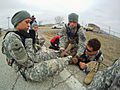 A Junior Reserve Officers' Training Corps cadet wraps a bandage around a fellow cadet's leg.jpg