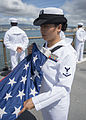 A U.S. Sailor folds the U.S. flag aboard the amphibious dock landing ship USS Pearl Harbor (LSD 52) May 25, 2013, as the ship leaves Pearl Harbor, Hawaii, for Samoa, the first mission port for Pacific 130525-N-SP369-030.jpg