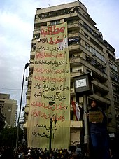 Large banner hanging from tall apartment building, with woman holding sign in foreground