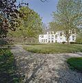 Achterzijde van het gebouw met bordes en groot wapen in de witgepleisterde gevel, park met houten fruitmuur - Ysbrechtum - 20406507 - RCE.jpg