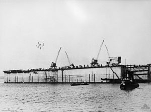 A photo of a rectangular structure with cranes mounted on it floating on a calm body of water. Several boats are visible in front of the structure.